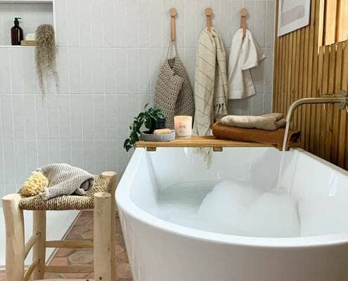 A large white bathtun filled with bubbles in a wooden scandi style bathroom