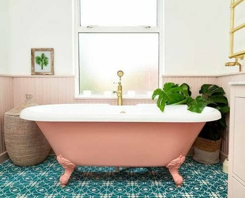 A colourful pink bath in a bright colourful scandi bathroom