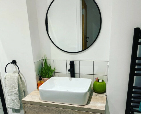 a small bathroom basin and vanity unit with a black tap