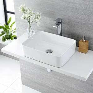 A square basin and a chrome tap in a grey bathroom