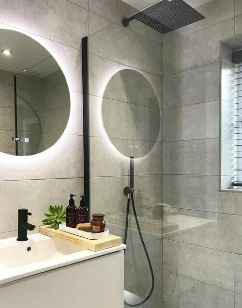 a scandi bathroom with a black shower and brassware finish