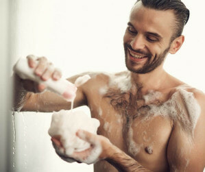 man washing with loofah
