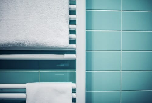 a close up of a bathroom towel radiator with towels draped over it