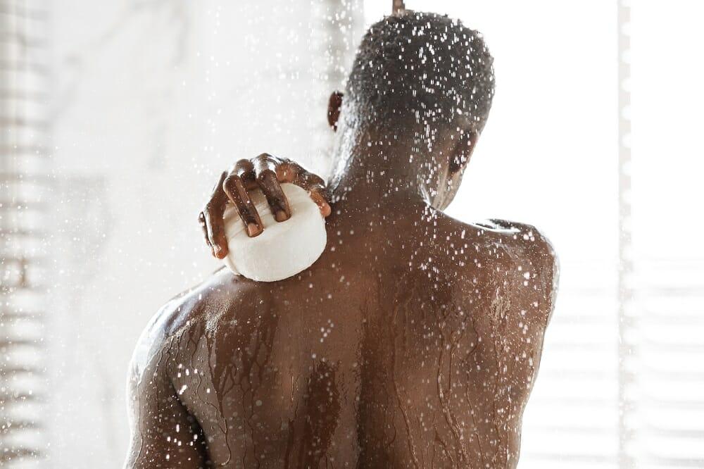 man washing back in shower
