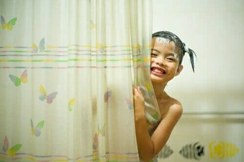 girl in the shower holding onto the shower curtain