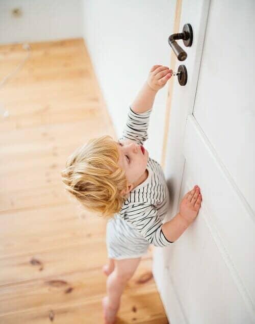 toddler opening a bathroom door
