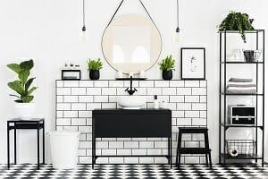 Mirror between plants above black washbasin in bathroom interior