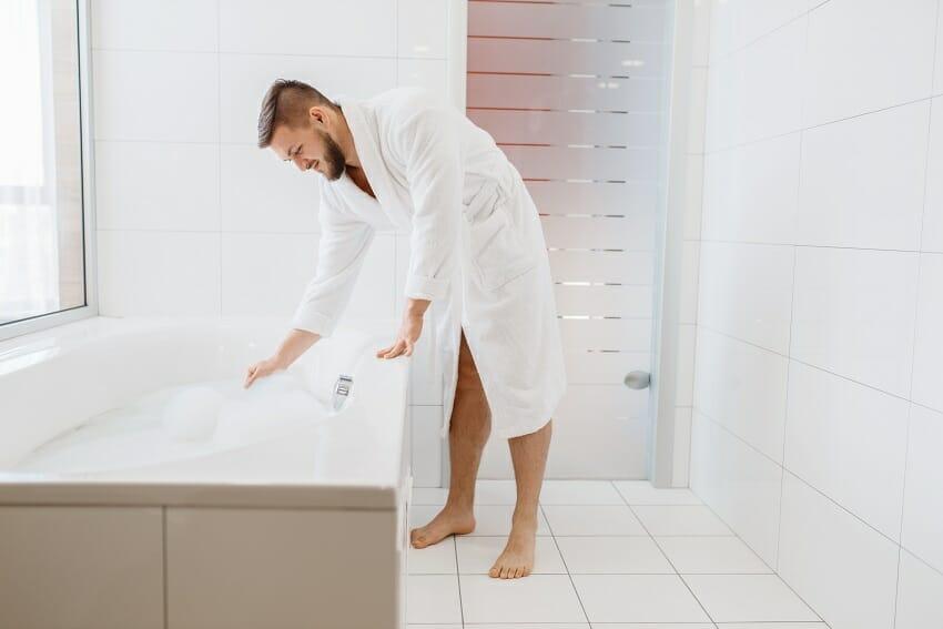 Man in bathrobe fills a bath with water and foam