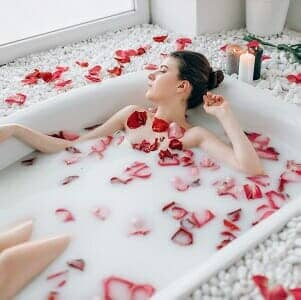 a woman lying in her bath being pampered