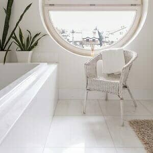 Spacious white hotel bathroom with round window