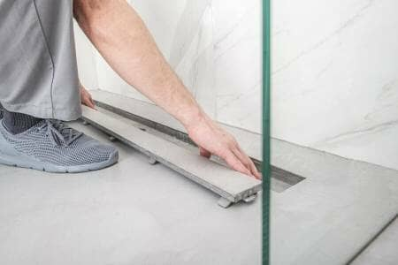 Linear shower drain being professionally installed