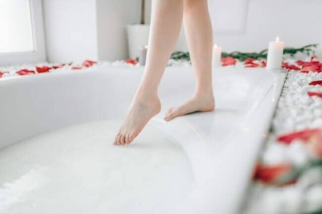 Een vrouw die haar teen in het badwater doopt